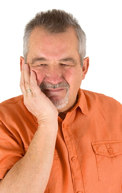 Man holding his cheek with unbearable pain from a toothache.