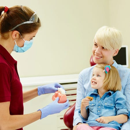 Nurse explaining to a young child how to develop healthy habits of good oral hygiene.