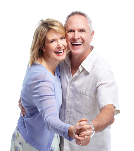 Older couple smiling with confidence after benefiting from implant retained dentures.