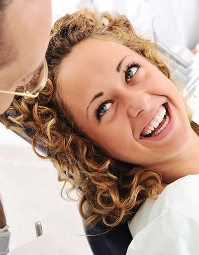 Woman smiling with confidence during a regular dental check-up.